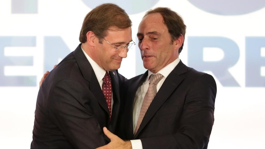 Portuguese Prime Minister Pedro Passos Coelho, left, and Deputy Prime Minister Paulo Portas hug each other after addressing supporters following the announcement of the results of Portugal's general elections Sunday, Oct. 4 2015, in Lisbon. Opinion polls prior to the vote predicted a close contest. (AP Photo/Armando Franca)