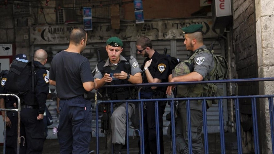 "An Israeli border policeman checks papers at the entrance to the Old City in Jerusalem on Sunday, Oct. 4, 2015. Israeli police barred Palestinians from Jerusalem's Old City on Sunday in response to stabbing attacks that killed two Israelis and wounded three others, as Israeli Prime Minister Benjamin Netanyahu vowed a ""harsh offensive"" to counter rising violence. (AP Photo/Mahmoud Illean)"