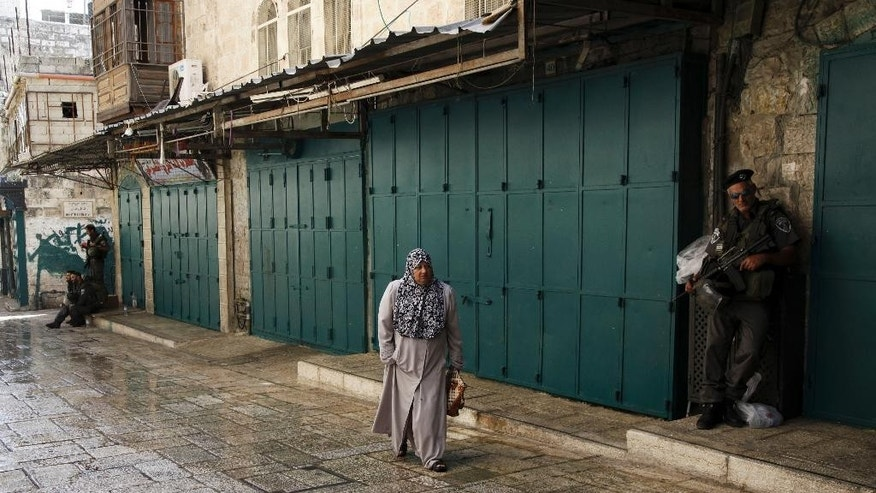 "Israeli border policemen stand guard as a Palestinian woman walks by in the Old City in Jerusalem on Sunday, Oct. 4, 2015. Israeli police barred Palestinians from Jerusalem's Old City on Sunday in response to stabbing attacks that killed two Israelis and wounded three others, as Israeli Prime Minister Benjamin Netanyahu vowed a ""harsh offensive"" to counter rising violence. (AP Photo/Mahmoud Illean)"