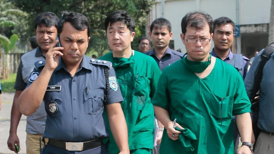 A Japanese doctor, front right, and the chief security officer of the Japanese embassy in Bangladesh, center walk back from the morgue after the autopsy on the body of killed Japanese citizen Kunio Hoshi at Mahiganj village in Rangpur district, 300 kilometers (185 miles) north of Dhaka, Bangladesh, Sunday, Oct. 4, 2015.  Bangladesh's government on Sunday rejected a claim by the Islamic State group that it was responsible for gunning down Kunio Hoshi. After assailants shot and killed the Japanese citizen in northern Bangladesh on Saturday, the Islamic State group issued a statement claiming responsibility for the attack, according to the SITE Intelligence Group, which monitors jihadi postings online. (AP Photo/A.M. Ahad)