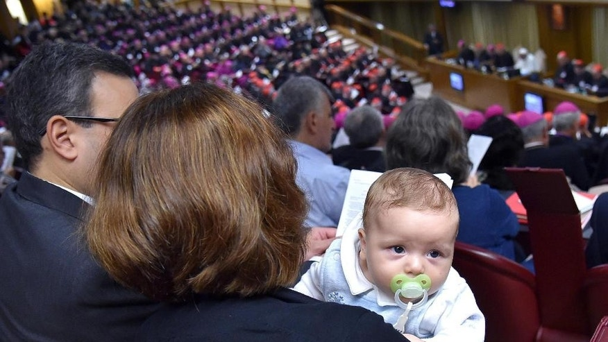 A couple with a baby attends the opening session of a two-week bishops' meeting on family issues, at the Vatican, Monday, Oct. 5, 2015. The Synod of bishops and cardinals from around the world is aimed at making the church's teaching on family life relevant to today's Catholic families. White figure in the background at top right is Pope Francis. (Ettore Ferrari/ANSA via AP) ITALY OUT