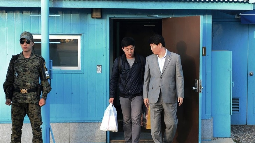 In this photo provided by the South Korean Unification Ministry, South Korean Won Moon Joo, center, who has a permanent resident status in the United States, is escorted by a South Korean official at the border village of Panmunjom in Paju, South Korea, Monday, Oct. 5, 2015. North Korea freed a South Korean national who'd been attending New York University before his detention, Seoul officials said Monday, in a possible sign Pyongyang wants better ties with rival Seoul and may back away from a recent threat to launch a long-range rocket later this month. (The South Korean Unification Ministry via AP)
