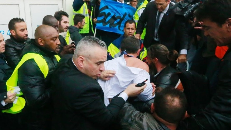 Air France director of Human Ressources, Xavier Broseta, center (back to the camera), protected by security guards tries to flee the Air France headquarters at Roissy Airport, north of Paris, France, during scuffles with union activists, Monday, Oct. 5, 2015. Union activists protesting proposed layoffs at Air France stormed the headquarters during a meeting about the job cuts, zeroing in on two managers who had their shirts torn from their bodies, scaled a fence and fled under police protection. (AP Photo/Jacques Brinon)
