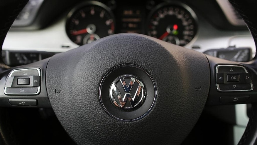 The VW sign of Germany's car company Volkswagen is fixed in the center of a steering wheel of a VW car photographed in, Berlin, Germany, Monday, Oct. 5, 2015. (AP Photo/Markus Schreiber)