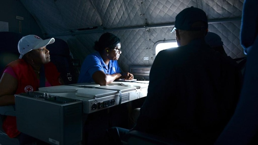 In this Saturday, Oct. 3, 2015, photo, provided by the U.S. Coast Guard, a U.S. aid worker looks out the window of an Air Station Miami HC-144 Ocean Sentry aircraft to observe damage caused by Hurricane Joaquin in the Bahamas. The HC-144 aircrew flew over several islands to survey and document damage. (Petty Officer 2nd Class Mark Barney/U.S. Coast Guard via AP)