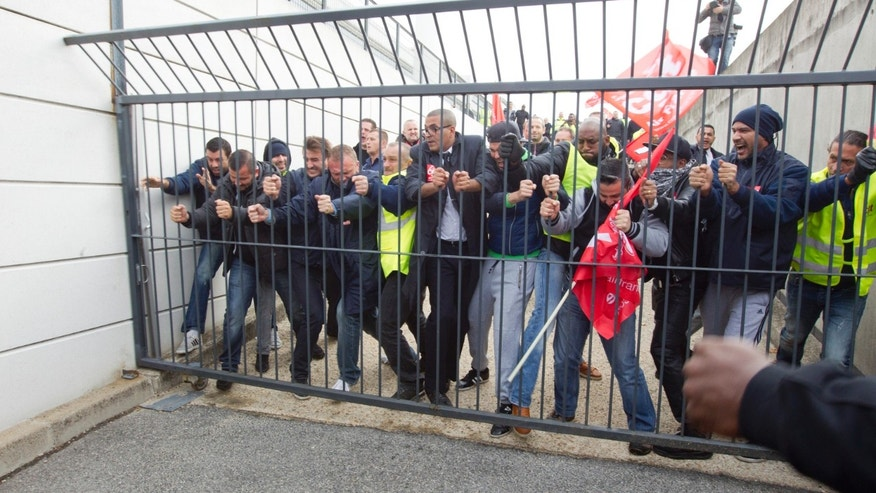 Oct. 5, 2015- Air France union activists break through a gate as they storm the headquarters to disturb a meeting at Roissy Airport, north of Paris. Union activists protesting proposed layoffs disrupted a meeting about job cuts.