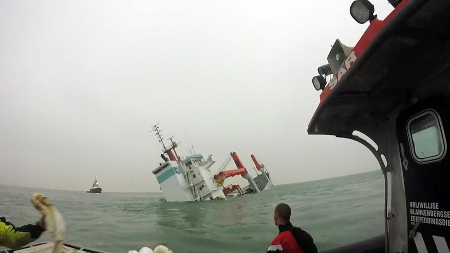 In this photo provided by the VBZR Vrijwillige Blankenbergse Zee Reddingsdienst, the Dutch cargo ship Flinterstar sinks off of the Belgian coast near Zeebrugge, Belgium on Tuesday, Oct. 6, 2015. The Dutch registered cargo ship sank off the Belgian coast after colliding with a gas tanker early Tuesday morning. The VBZR is a government approved search and rescue organization run entirely by volunteers. (VBZR Vrijwillige Blankenbergse Zee Reddingsdienst via AP)