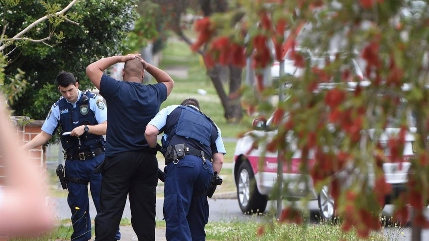 Police pull over and search a man and his vehicle near a house which was raided earlier Wednesday morning on Bursill Street at Guildford in Sydney's west, Oct. 7, 2015. Police arrested five people during a series of raids on Wednesday in connection with the slaying of a civilian police worker, which officials have said they believe was linked to terrorism. (Dean Lewins/AAP Image via AP) NO ARCHIVING, AUSTRALIA OUT, NEW ZEALAND OUT, PAPUA NEW GUINEA OUT, SOUTH PACIFIC OUT