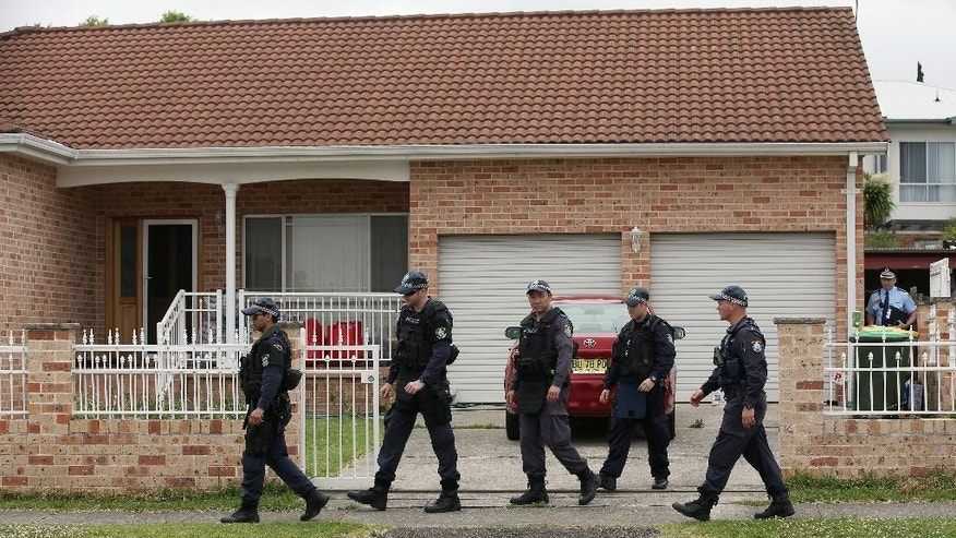 Police walk around a property in the suburb of Guildford in Sydney, Wednesday, Oct. 7, 2015. Police arrested five people during a series of raids Wednesday in connection with the slaying of a civilian police worker, which officials have said they believe was linked to terrorism. (AP Photo/Rick Rycroft)