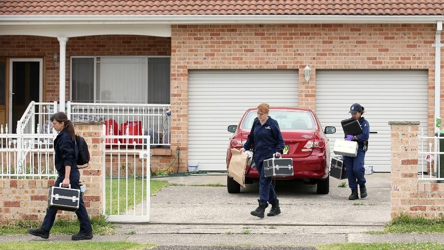 Police investigators leave a property in the suburb of Guildford in Sydney, Wednesday, Oct. 7, 2015. Police arrested five people during a series of raids Wednesday in connection with the slaying of a civilian police worker, which officials have said they believe was linked to terrorism. (AP Photo/Rick Rycroft)