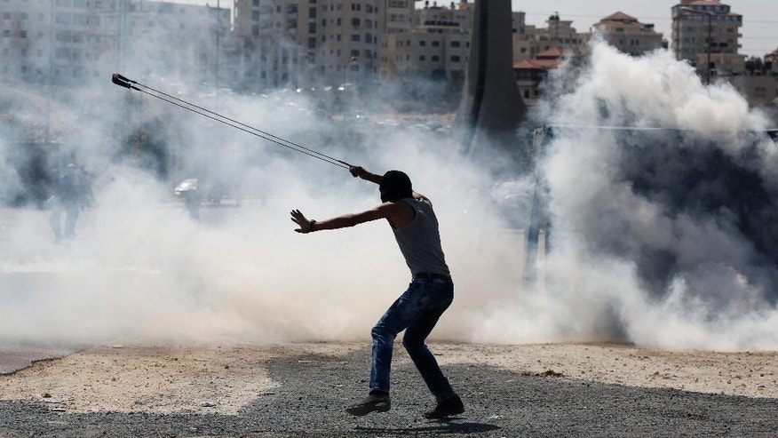 A Palestinian demonstrator uses a slingshot during clashes following a demonstration in the West Bank city of Ramallah, Monday, Oct. 5, 2015. Two Palestinian youths were killed in clashes with Israeli soldiers in the West Bank on Monday as fears spread of a further escalation in violence that has already killed several Israeli civilians and wounded hundreds of Palestinian protesters over the past days. The Red Crescent says 456 Palestinians have been injured in the violent protests over the last two days alone. (AP Photo/Nasser Shiyoukhi)