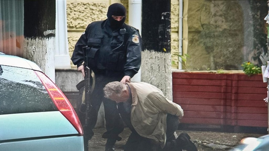 "In this June 27, 2011 photo provided by the Moldova General Police Inspectorate, Teodor Chetrus is detained by a police officer in Chisinau, Moldova during a uranium-235 sting operation. In many of the smuggling cases in this former Soviet republic, ringleaders insulated themselves through a complex network of middlemen to shield the bosses from arrest. In this case, Chetrus was the go-between. Former Moldova Police investigator Constantin Malic recalls that Chetrus said, ""I really want an Islamic buyer because they will bomb the Americans."" (Moldova Police via AP)"
