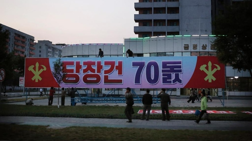 In this Oct. 6, 2015 photo, people put up a sign board marking the upcoming 70th anniversary of the founding of North Korea's Workers' Party in Pyongyang, North Korea. While North Korea prepares a big show to mark the 70th anniversary of the ruling Workers' Party, the daily struggles of life outside the capital - such as finding clean running water and putting nutritious food on the table year-round - pose a harsh, but largely unseen, contrast to the grand celebrations the world will see Oct. 10. (AP Photo/Charles Dharapak)