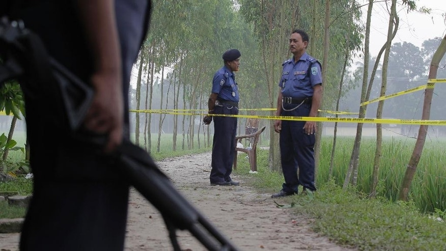 FILE- In this Sunday, Oct. 4, 2015 file photo, Bangladeshi security officers stand by the site where Japanese citizen Kunio Hoshi was killed Saturday at Mahiganj village in Rangpur district, 300 kilometers (185 miles) north of Dhaka, Bangladesh. Closely following the fatal attacks on two foreigners last week, a Bangladeshi pastor Monday survived an attempt on his life by three men who came to his home pretending to want to learn about Christianity, police and the victim said Tuesday.(AP Photo/A.M. Ahad, file)