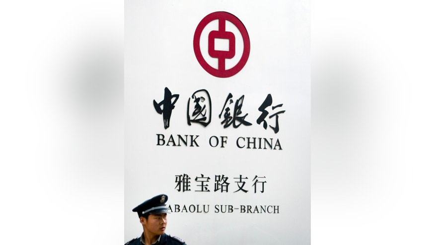 FILE - In this May 11, 2015 file photo, a security guard stands outside a Bank of China branch in Beijing. A New York judge has ordered the Bank of China to hand over detailed information about Chinese bank accounts used by a counterfeiting ring that allegedly sold millions of dollars of fake Gucci handbags and wallets in the U.S. (AP Photo/Mark Schiefelbein, File)