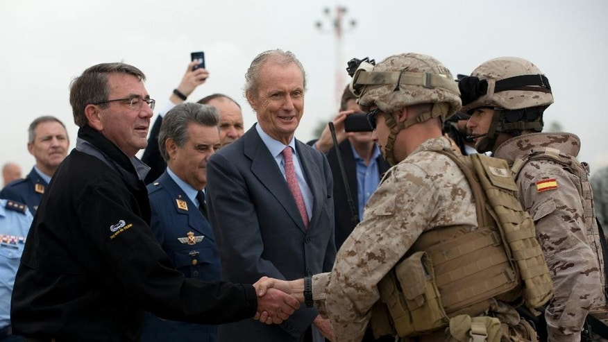 US Secretary of Defense Ashton Carter, left, shakes hands with a US Marine, next to Spain's Defense Minister Pedro Morenes, center, during their visit at Moron Airbase, near Seville, Spain, Tuesday, Oct. 6, 2015. Carter is on a weeklong trip to Europe, including stops in Spain, Italy and London, and will also attend the NATO meeting, which is expected to focus on Russia's recent launch of military airstrikes in Syria. (AP Photo/Laura Leon)