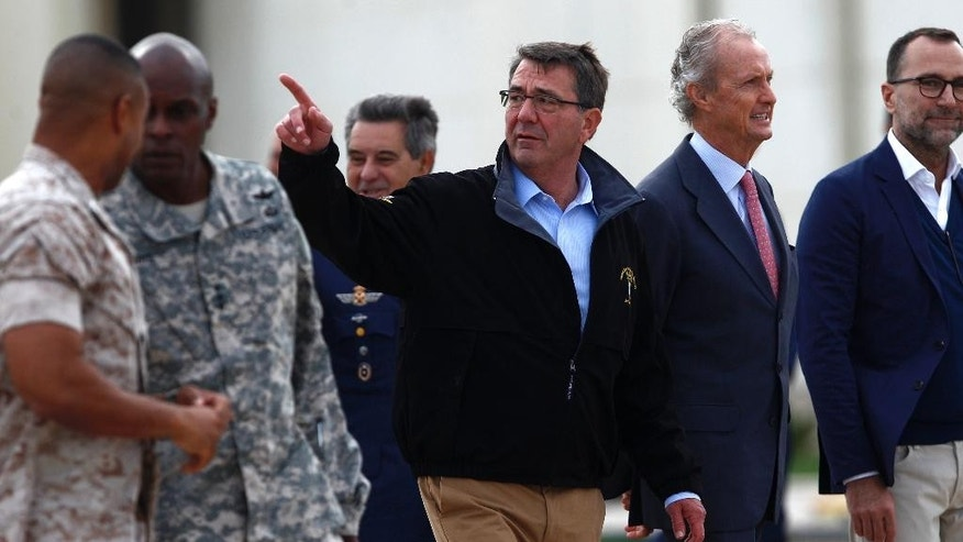US Secretary of Defense Ashton Carter, center, and Spain's Defense Minister Pedro Morenes, right, walk together during their visit at Moron Airbase, near Seville, Spain, Tuesday, Oct. 6, 2015. Carter is on a weeklong trip to Europe, including stops in Spain, Italy and London, and will also attend the NATO meeting, which is expected to focus on Russia's recent launch of military airstrikes in Syria. (AP Photo/Laura Leon)