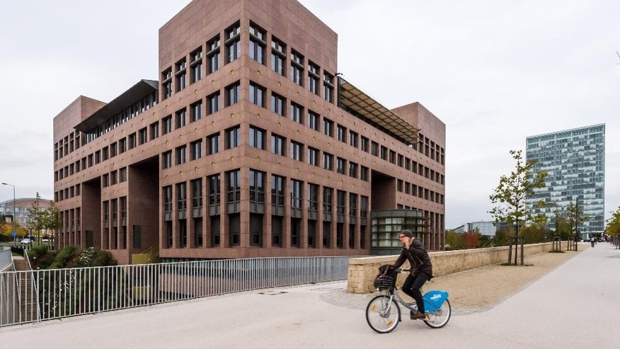 In this photo taken on Monday, Oct. 5, 2015 a man rides his bike by the European Court of Justice in Luxembourg. Europe's highest court has ruled in favor of an Austrian law student who claims a trans-Atlantic data protection agreement doesn't adequately protect consumers. (Geert Vanden Wijngaert)