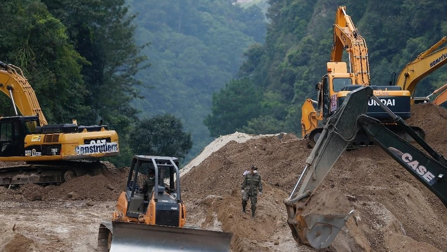 Bulldozers move land for a fourth day to search for victims of a fatal mudslide in Cambray, a neighborhood in the suburb of Santa Catarina Pinula, on the outskirts of Guatemala City, Monday, Oct. 5, 2015. Hope faded for many families that they would find survivors, as the smell of rotting bodies spread across the enormous mound of earth, and rescuers reported the buried dwellings they reached were filled with water, suggesting anyone trapped inside would have drowned. (AP Photo/Moises Castillo)
