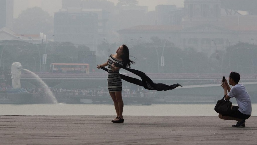 In the Thursday, Sept. 10, 2015, file photo, a woman poses for photos during a hazy day in Singapore.  Scientists predict the haze this year is on track to surpass 1997 levels when pollution soared to record highs in an environmental disaster that cost an estimated $9 billion. A bad bout of haze resembles wintry fog, but laced with tiny particles of ash that are particularly harmful to the elderly, children and those with chronic heart and lung conditions. (AP Photo/Ng Han Guan, File)