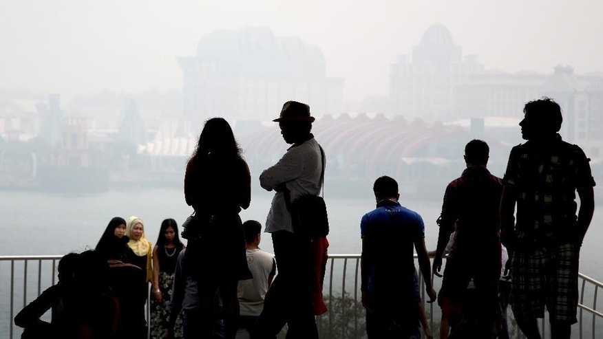 In this Thursday, Sept. 24, 2015, file photo, tourists are silhouetted as they view Singapore's popular tourist destination, Sentosa, as seen through the haze in the background, in Singapore. Scientists predict the haze this year is on track to surpass 1997 levels when pollution soared to record highs in an environmental disaster that cost an estimated $9 billion. A bad bout of haze resembles wintry fog, but laced with tiny particles of ash that are particularly harmful to the elderly, children and those with chronic heart and lung conditions. (AP Photo/Wong Maye-E, File)