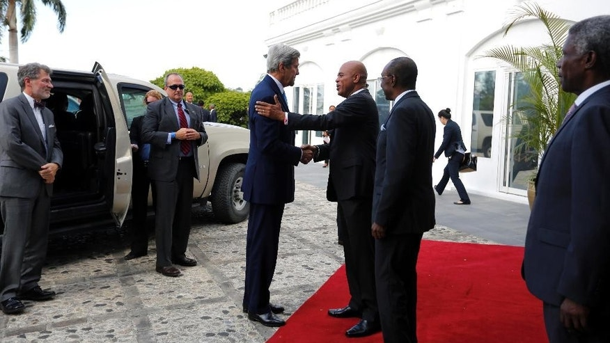 U.S. Secretary of State John Kerry, center, shakes hand with Haiti's President Michel Martelly at his arrival at the national Palace in Port-au-Prince, Haiti, Tuesday, October 6, 2015. Kerry stopped briefly in Haiti to discuss preparations for the country's upcoming presidential and parliamentary elections. ( AP Photo/Dieu Nalio Chery)