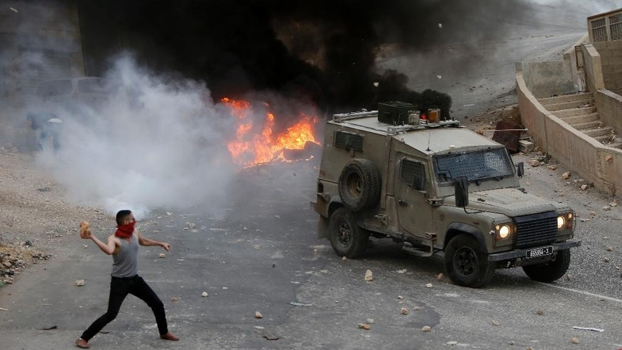 "Palestinian youths throw rocks at Israeli military vehicle during a raid in the West Bank city of Nablus, Tuesday, Oct. 6, 2015. Israeli Prime Minister Benjamin Netanyahu warned Monday that he will use a ""strong hand"" to quell violent Palestinian protests and deadly attacks, signaling that the current round of violence is bound to escalate at a time when a political solution to the conflict is increasingly distant. (AP Photo/Majdi Mohammed)"