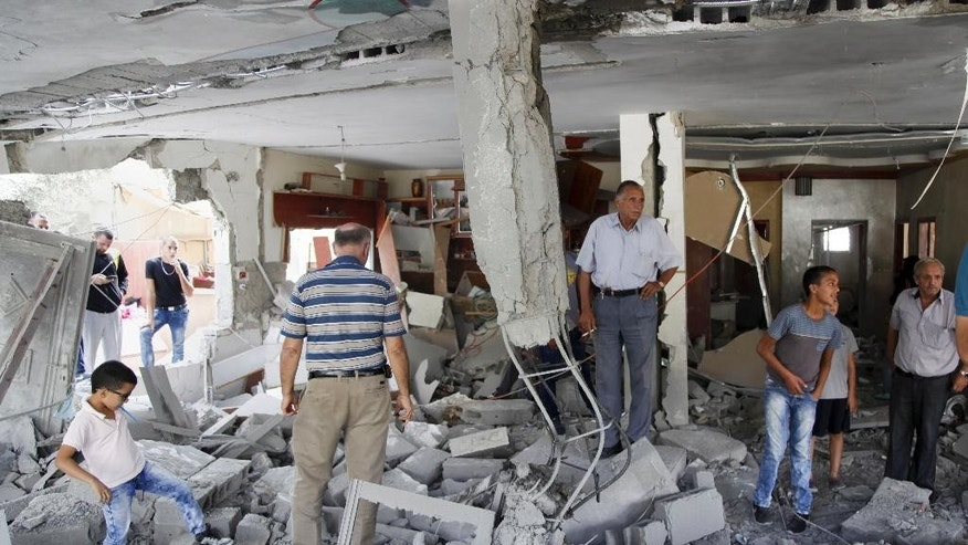 Palestinians inspect the home of the Abu Jaber family that was demolished by the Israeli military in east Jerusalem, Tuesday, Oct. 6, 2015. The Israeli military on Tuesday demolished homes of two Palestinian militants in east Jerusalem, one of which belonged to family of Ghassan Abu Jaber who killed four worshippers in an attack on a synagogue last year. Although Ghassan Abu Jaber was immediately killed, Israel often carries out such demolitions of the homes of militants' families, believing it will deter future attacks. (AP Photo/Mahmoud Illean)