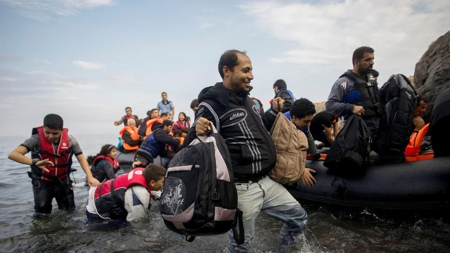 Migrants arrive with an overloaded rubber dinghy from Turkey on the coast of Lesbos island, Greece, Tuesday, Oct. 6, 2015. (Zoltan Balogh/MTI via AP)