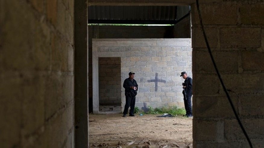 FILE - In this Thursday, July 3, 2014, file photo, state police stand inside a warehouse where a black cross covers a wall near blood stains on the ground, after a shootout between Mexican soldiers and alleged criminals on the outskirts of the village of San Pedro Limon, in Mexico state, Mexico. It was confirmed on Monday, Oct. 5, 2015, that a Mexican judge ruled that there is insufficient evidence to try four of the seven soldiers charged in the case of 22 suspects killed in 2014, some of whom were apparently shot after they surrendered.  (AP Photo/Rebecca Blackwell, File)