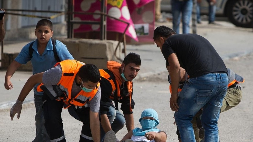 Palestinians carry an injured man during clashes with Israeli troops at Qalandia checkpoint between Jerusalem and the West Bank city of Ramallah, Tuesday, Oct. 6, 2015. A new generation of angry, disillusioned Palestinians is driving the current wave of clashes with Israeli forces: They are too young to remember the hardships of life during Israel's clampdown on the last major uprising, and after years of nationalist Israeli governments many have lost faith in statehood through negotiations and believe Israel only understands force. (AP Photo/Majdi Mohammed)