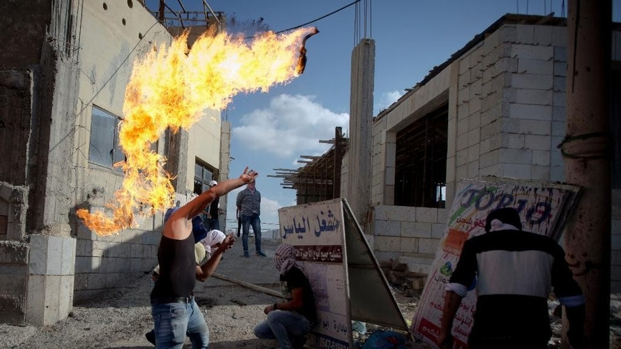 A Palestinian throws a Molotov cocktail during clashes with Israeli troops at Qalandia checkpoint between Jerusalem and the West Bank city of Ramallah, Tuesday, Oct. 6, 2015. A new generation of angry, disillusioned Palestinians is driving the current wave of clashes with Israeli forces: They are too young to remember the hardships of life during Israel's clampdown on the last major uprising, and after years of nationalist Israeli governments many have lost faith in statehood through negotiations and believe Israel only understands force. (AP Photo/Majdi Mohammed)