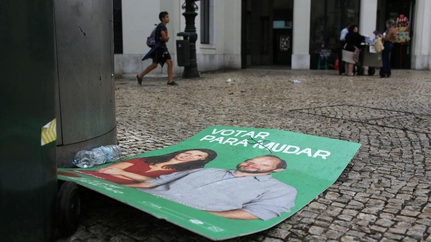 "An election campaign poster with the slogan ""Vote to change"" lies on the ground in Lisbon, Monday, Oct. 5 2015, the day after Portugal's general elections. The poster belongs to the new leftist party Livre, or Free, which failed to win any seats in parliament. The center-right coalition government won Sunday's ballot despite its unpopular austerity policies. (AP Photo/Armando Franca)"