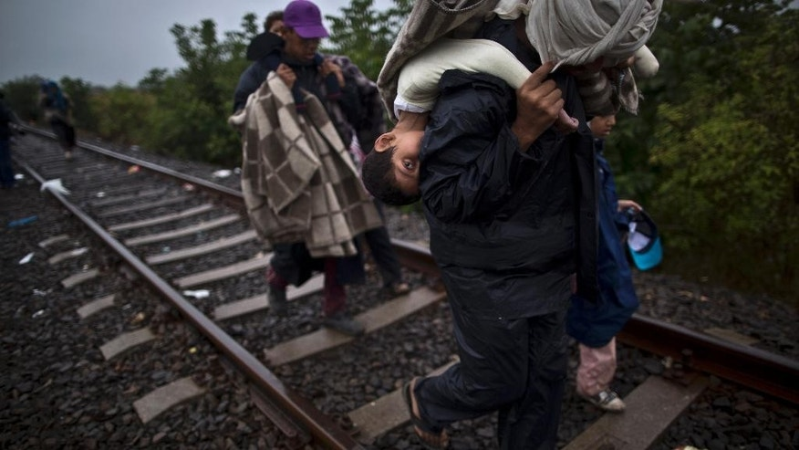 In this Friday, Sept. 11, 2015 photo, Bara'ah Alhammadi, 10, a Syrian migrant, is carried on the back of her father as they make their way along a railway track after crossing the Serbian-Hungarian border near Roszke, southern Hungary. Tens of thousands of people trying to escape conflict and poverty in places like Syria and Afghanistan have been making their way across Europe this summer and fall, embarking on grueling journeys that typically start with a short boat trip from Turkey to Greece, then continue north and west on foot and by bus and train. (AP Photo/Muhammed Muheisen)