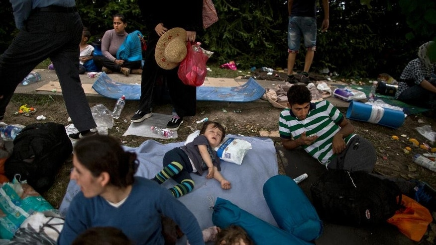 In this Saturday, Sept. 19, 2015 photo, migrants from Syria and Iraq rest on a roadside while hoping to board a bus in Tovarnik, Croatia. Tens of thousands of people trying to escape conflict and poverty in places like Syria and Afghanistan have been making their way across Europe this summer and fall, embarking on grueling journeys that typically start with a short boat trip from Turkey to Greece, then continue north and west on foot and by bus and train. (AP Photo/Muhammed Muheisen)