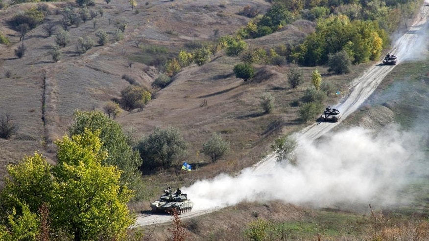 Ukrainian army tanks roll from the front line near the village of Krymske, Luhansk region, Eastern Ukraine, Monday, Oct. 5, 2015. A summit reviving a European push to bring peace to eastern Ukraine ended Friday with a call for the delay of contentious rebel plans to hold local elections this month and for both sides to begin a promised withdrawal of smaller-caliber weapons.  (AP Photo/Inna Varenytsia)