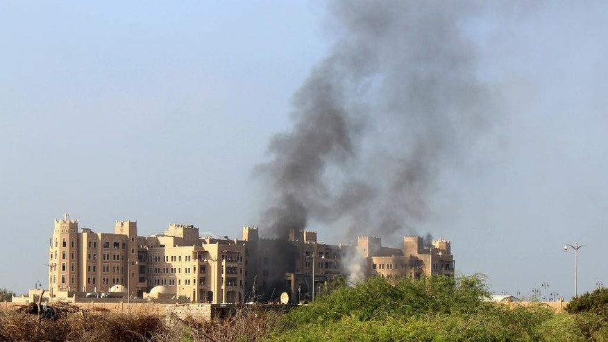 Smoke rises following an explosion that hit Hotel al-Qasr where Cabinet members and other government officials are staying, in the southern port city of Aden, Yemen, Tuesday, Oct. 6, 2015. Security officials, who work for Yemen's internationally recognized government said three explosions have hit Aden and there are casualties in Tuesday's explosions but they had no specifics or details. (AP Photo/Wael Qubady)