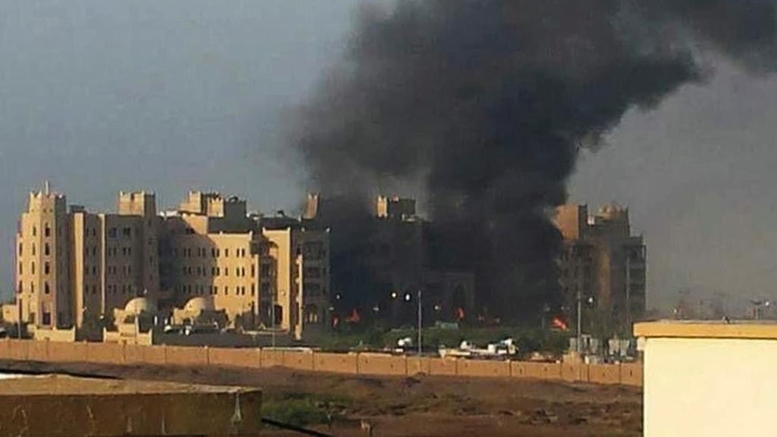 In this photo provided by the Emirates News Agency, WAM, smoke rises following an explosion that hit Hotel al-Qasr, where Cabinet members and other government officials are staying, in the southern port city of Aden, Yemen, Tuesday, Oct. 6, 2015. A new Islamic State affiliate in Yemen has claimed responsibility for attacks in Aden that killed at least 15 people. (WAM via AP)