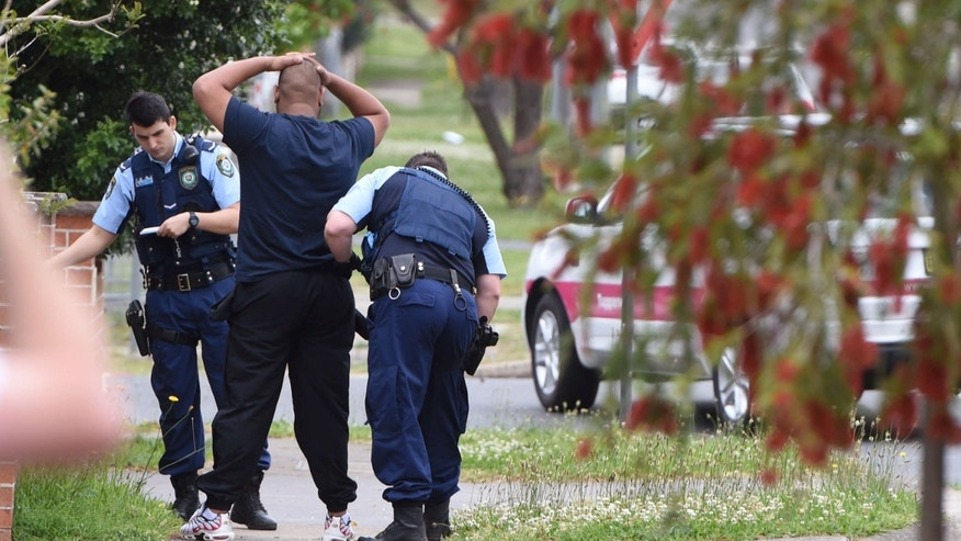 Oct. 7, 2015: Police pull over and search a man and his vehicle near a house which was raided earlier Wednesday morning on Bursill Street at Guildford in Sydney's west.
