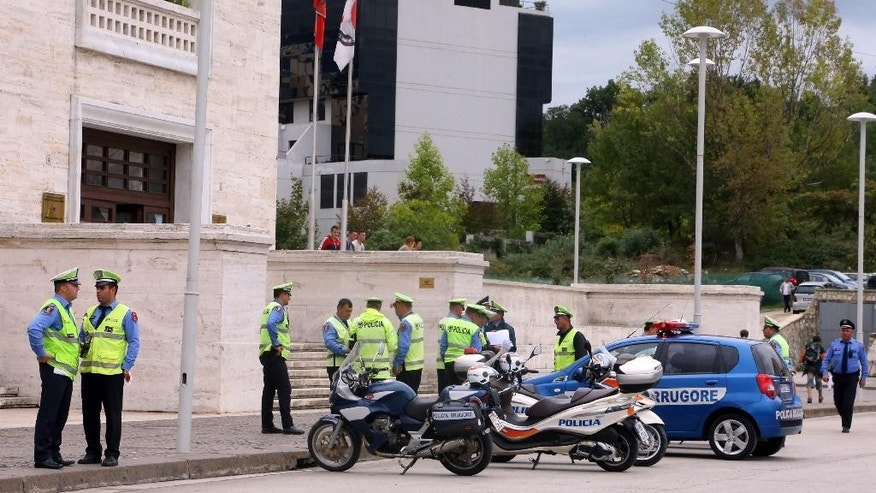 Police secure the area around the hotel, where Serbian national soccer team will stay, in Tirana on Wednesday, Oct. 7, 2015, as authorities have enforced tough security measures ahead of Thursday's soccer game.  Police in Albania say they have arrested a man who claimed to have flown a drone carrying a nationalist banner over a stadium in Serbia last year during a European qualifier, in an incident that prompted fan violence and a diplomatic spat between the two countries.  (AP Photo/Hektor Pustina)