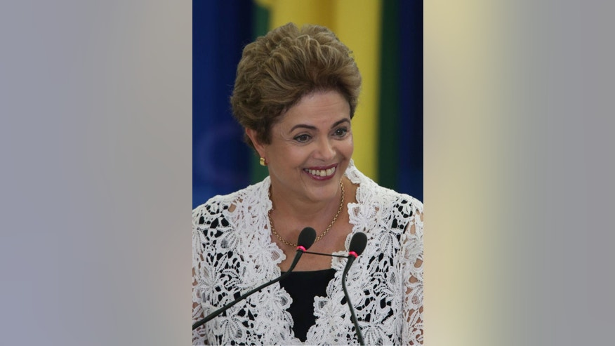 Brazil's President Dilma Rousseff smiles during the swearing in ceremony of her new government ministers at the Planalto Presidential Palace, in Brasilia, Brazil, Monday, Oct. 5, 2015. Rousseff shook up her cabinet amid the biggest political and economic crisis besetting Latin America's largest economy. (AP Photo/Eraldo Peres)
