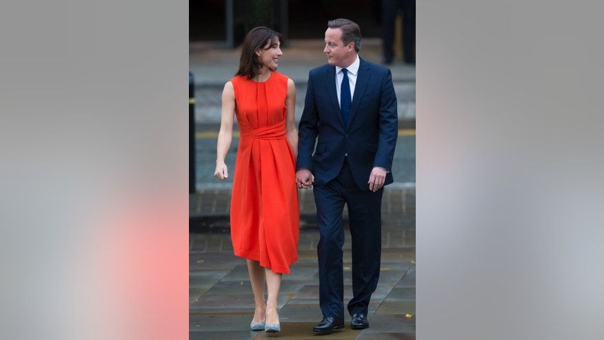 Britain's Prime Minister David Cameron, right and his wife Samantha make their way to the conference hall before his keynote speech at the annual Conservative Party Conference in Manchester, England, Wednesday Oct. 7, 2015. (AP Photo/Jon Super)