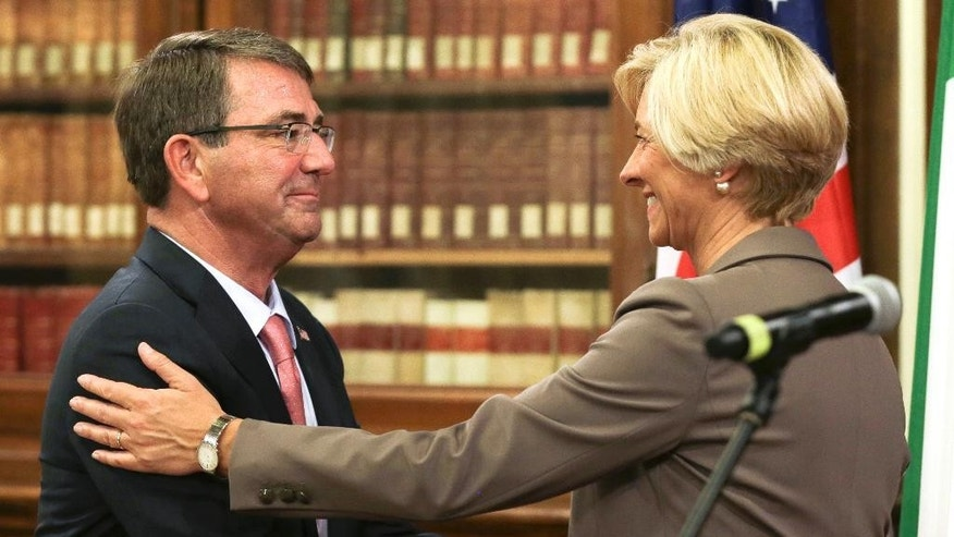 Italian Defense Minister Roberta Pinotti, right, and US Secretary of Defense Ashton Carter shake hands at the end of joint press conference on the occasion of their bilateral meeting, in Rome, Wednesday, Oct. 7, 2015.  (AP Photo/Andrew Medichini)