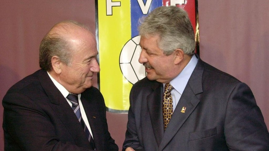 FILE - In this Nov. 8, 2004 file photo Sepp Blatter, President of the FIFA, left, shakes hands with the President of the Venezuelan Soccer Federation, Rafael Esquivel, in Caracas, Venezuela. A senior South American soccer official has been denied bail on health grounds in Switzerland as he fights extradition to the United Sates after being indicted in the FIFA bribery case. CONMEBOL vice president Rafael Esquivel of Venezuela, one of seven soccer officials arrested in Zurich in May, is currently in hospital in Switzerland, the Federal Office of Justice told The Associated Press on Monday, Oct. 5, 2015. (AP Photo/Leslie Mazoch, File)