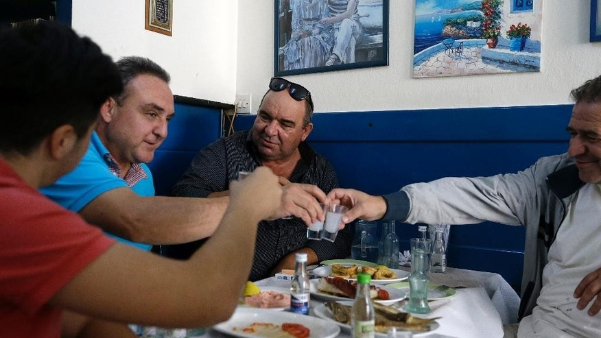 In this photo taken on  Monday, Oct. 5, 2015, customers  at a tavern clink glasses filled with tsipouro in Tirnavos, central Greece. The European Union has given Greece two months to double taxes on tsipouro, arguing it does not have the right to keep a reduced duty that is reserved for some traditionally made products. It also wants Athens to crack down on small independent producers who pay a low tax rate that is aimed at helping small producers but is now widely abused for bulk supply to small restaurants nationally. (AP Photo/Thanassis Stavrakis)