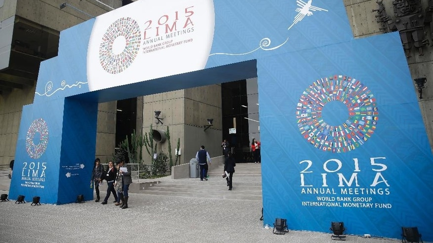 People pass under a welcome sign for the IMF and World Bank annual meetings in Lima, Peru, Tuesday, Oct. 6, 2015. The meetings are taking place Oct. 6-11. (AP Photo/Martin Mejia)