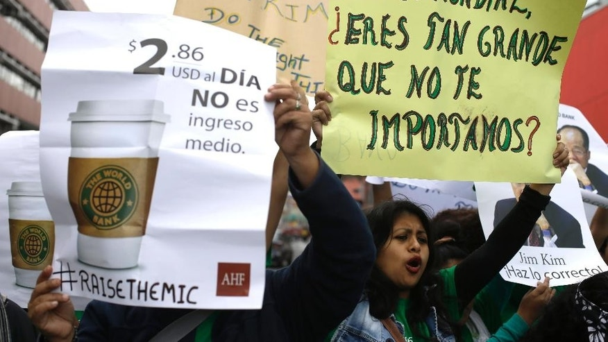 """Demonstrators hold messages near the site where the World Bank and International Monetary Fund are holding their annual meetings in Lima, Peru, Wednesday, Oct. 7, 2015. The sign at left reads in Spanish """"$2.86 U.S. dollars a day is not middle class income."""" At right reads """"World Bank. Are you so big you don't care about us?""""  (AP Photo/Martin Mejia)"""