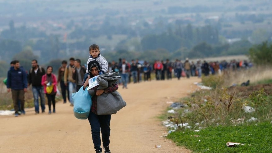 Migrants walk from the Macedonian border into Serbia, near the village of Miratovac, Serbia, Wednesday, Oct. 7, 2015. Several Eastern European countries are cooperating on controlling the flow of migrants at the external borders of the European Union, Zsolt Nemeth, head of the Hungarian parliament's foreign relations committee said Tuesday could set an example for the rest of the 28-nation bloc.  (AP Photo/Darko Vojinovic)
