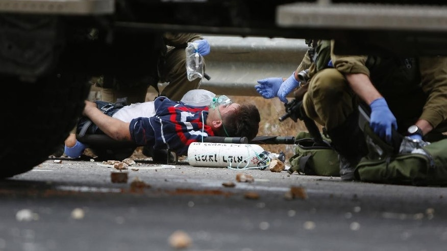 """Israeli soldiers treat wounded Palestinians during clashes with the Israeli military, near Ramallah, West Bank, Wednesday, Oct. 7, 2015. Israel's prime minister says he is calling off a planned trip to Germany because of a wave of violence between Israelis and Palestinians. A statement from Benjamin Netanyahu's office Wednesday said the Israeli leader would not depart for the two-day visit so that he could """"closely monitor the situation."""" (AP Photo/Majdi Mohammed)"""