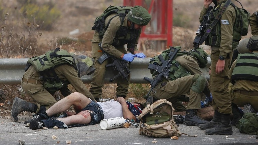 """Israeli soldiers treat a wounded Palestinian during clashes with the Israeli military, near Ramallah, West Bank, Wednesday, Oct. 7, 2015. Israel's prime minister says he is calling off a planned trip to Germany because of a wave of violence between Israelis and Palestinians. A statement from Benjamin Netanyahu's office Wednesday said the Israeli leader would not depart for the two-day visit so that he could """"closely monitor the situation."""" (AP Photo/Majdi Mohammed))"""